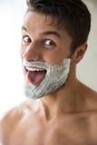 Mann mit Schaum auf dem Gesicht, das sein tonque zeigt lizenzfreie stockbilder