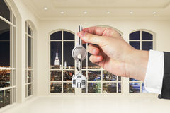 Mann mit Schlüssel in der Hand im modernen weißen leeren Raum mit Nachtstadt Lizenzfreies Stockfoto