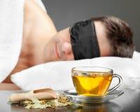 Mann mit Schlafenschablonenschlaf auf einem Bett Lizenzfreie Stockfotos
