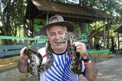 Mann mit Schlange um seinen Hals stockfoto
