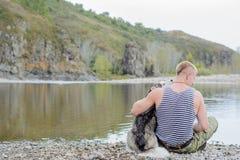 Mann mit Schlittenhund Stockbild