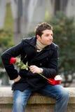 Mann mit Schokoladen und einer Rose, die oben gestanden wird Stockfotos
