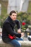 Mann mit Schokoladen und einer Rose, die oben gestanden wird Lizenzfreie Stockfotografie