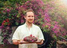 Mann mit Schokoladenkuchen im Garten Stockbild