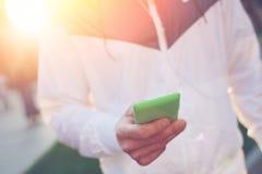 Mann mit Schreibentext des Handys und Gehen auf die Straße bei Sonnenuntergang Stockbilder