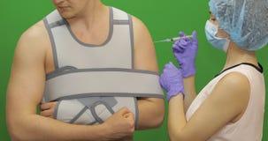 Mann mit Schulterverletzung Krankenschwester macht Stichel von den Schmerz Verbandfestlegungsschulter stockfotografie