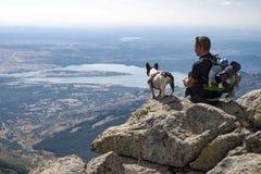 Mann mit seinem Hund, der die Ansichten genießt lizenzfreie stockfotografie