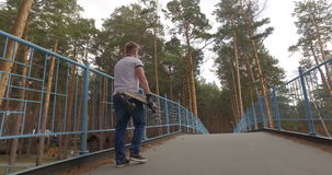 Mann mit seinem longboard gehend in einen Park Spurhaltung des Schusses stock footage