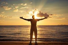 Mann mit seinen Händen oben zur Sonnenuntergangzeit Stockfotos