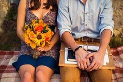 Mann mit Sketchbook und Frau mit einem Blumenstrauß, der auf einem Plaid sitzt lizenzfreie stockbilder