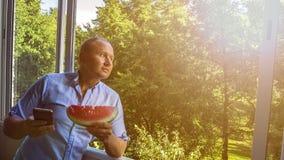 Mann mit smarphone und Wassermelone lizenzfreie stockfotografie