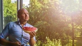 Mann mit smarphone und Wassermelone stockfotografie