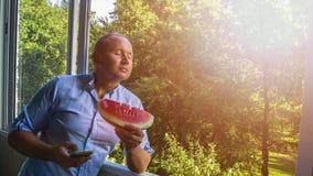 Mann mit smarphone und Wassermelone stockbild
