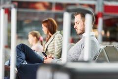 Mann mit Smartphone wartet in Flughafenruhezone stockfoto