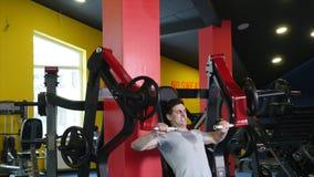 Mann mit Sport stellen das Handeln von Übung auf Simulator in der Turnhalle dar stock video footage