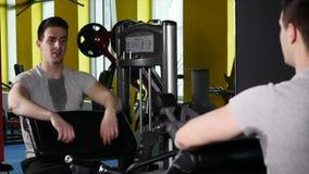 Mann mit Sport stellen das Handeln von Übung auf Simulator in der Turnhalle dar stock footage