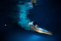 Mann mit Spritzenschwimmen unter dunkelblauem Wasser Stockbilder