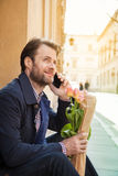 Mann mit Stangenbrot- und Blumenblumenstrauß sprechend an einem Handy - Stadt Lizenzfreie Stockbilder