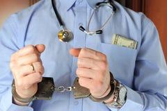 Mann mit Stethoskop hält seine Hände in den Handschellen vor sich Lizenzfreie Stockbilder