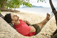 Mann mit Stoppel liegt auf schwarzer Hängematte auf Sandstrand stockfoto
