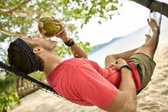 Mann mit Stoppel trinkt von der Kokosnuss auf Hängematte auf Sandstrand lizenzfreie stockbilder