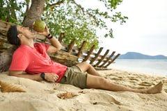 Mann mit Stoppel trinkt von der Kokosnuss auf Sandstrand stockfotos
