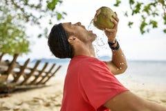 Mann mit Stoppel trinkt von der Kokosnuss auf Sandstrand stockbilder