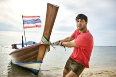 Mann mit Stoppel zieht hölzernes Boot durch Seil auf Sandstrand lizenzfreie stockfotografie