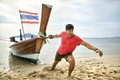 Mann mit Stoppel zieht hölzernes Boot durch Seil auf Sandstrand stockfotografie