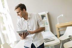 Mann mit Tablette im Büro Stockfotos