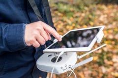 Mann mit Tablette und Brummenkontrolleur im Herbst parken lizenzfreie stockfotos
