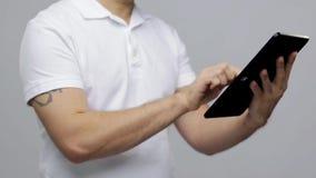 Mann mit Tabletten-PC über grauem Hintergrund stock video