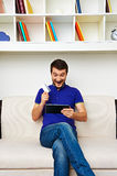 Mann mit Tabletten-PC und -Kreditkarte zu Hause Lizenzfreie Stockfotos