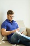 Mann mit Tabletten-PC zu Hause Stockbild