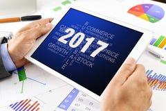 Mann mit Tag-Cloud von Zielen für 2017 in der Tablette Stockfoto