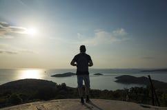 Mann mit Tasche auf hinterem schauendem Ozean bei Sonnenuntergang in Kroatien Stockfotos