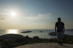 Mann mit Tasche auf hinterem schauendem Ozean bei Sonnenuntergang in Kroatien Stockbild