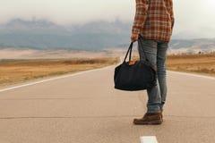 Mann mit Tasche in der Hand gehend hinunter eine Gebirgsstraße Lizenzfreies Stockbild
