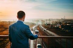 Mann mit Tasse Kaffee auf der Brücke Früher Morgen, der Sonnenaufgang, verschwindet die Straße im Abstand stockfotografie