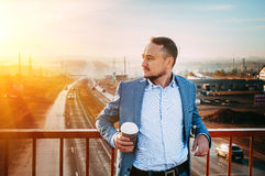 Mann mit Tasse Kaffee auf der Brücke Früher Morgen, der Sonnenaufgang, verschwindet die Straße im Abstand Lizenzfreies Stockfoto