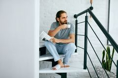 Mann mit Tasse Kaffee-Lesezeitung zu Hause stockfotos