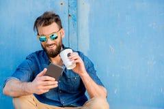 Mann mit Telefon auf dem blauen Hintergrund Lizenzfreies Stockfoto