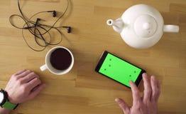 Mann mit trinkendem Tee des Smartphone Lizenzfreies Stockbild