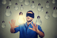 Mann mit verbundenen Augen, der durch die Glühlampen suchen nach guter Idee geht lizenzfreies stockfoto