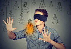 Mann mit verbundenen Augen, der durch die Glühlampen suchen nach Idee geht Lizenzfreies Stockfoto