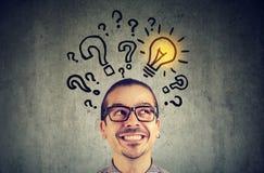 Mann mit vielen Fragen und Glühlampe der Lösung über Kopf lizenzfreie stockfotos