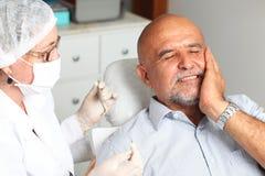 Mann mit Zahnschmerzen am Zahnarzt lizenzfreie stockfotografie
