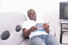Mann mit Zeitschrift auf Sofa lizenzfreie stockfotografie