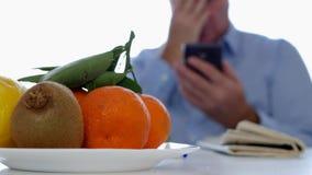 Mann mit Zeitungen und Früchte simsen auf dem Tisch unter Verwendung der Mobiltelefon-Kommunikation stock video footage