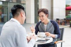 Mann mit zwei Asiaten, der im Café und in der Diskussion sitzt stockfotografie